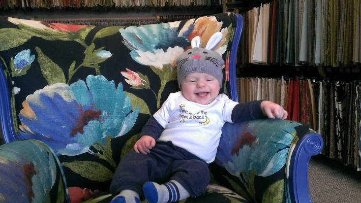 baby on floral upholstered chair